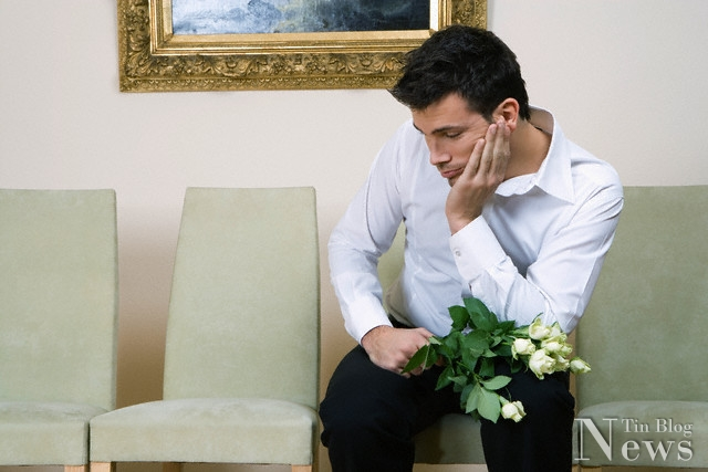 Lonely man waiting with bunch of flowers